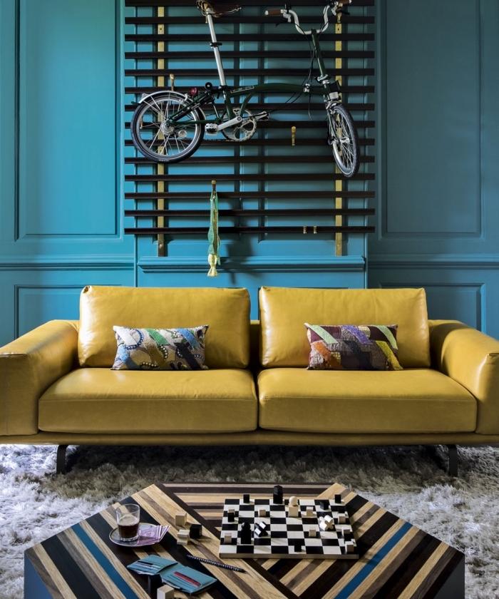 peinture bleu pétrole associée à un canapé jaune moutarde en cuir pour dynamiser le salon et lui apporter un look vintage chic
