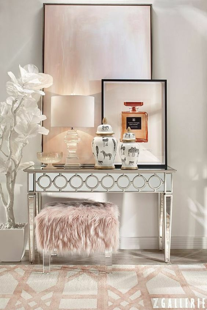 deco rose poudré dans un boudoir, meuble de toilette brillant en métal doré, tabouret bas carré recouvert de pelage au poil long en rose pale, panneau au cadre noir fin avec des nuances nacrées roses et blanches