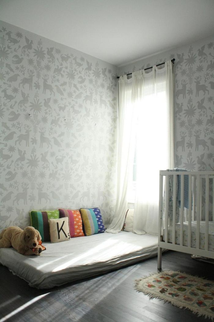 chambre en couleurs claires et lumineuse, lit bébé sans barreau, mur en papier peint gris perle avec des motifs animaux sauvages en taupe, lit partiellement en barreaux