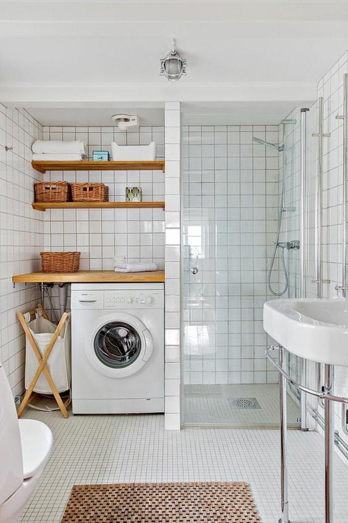 cloison verriere, verriere douche, lave-linge avec hublot, étagères en bois marron, carrelage blanc, lavabo blanc sur des pieds en aluminium, tapis en marron et noir