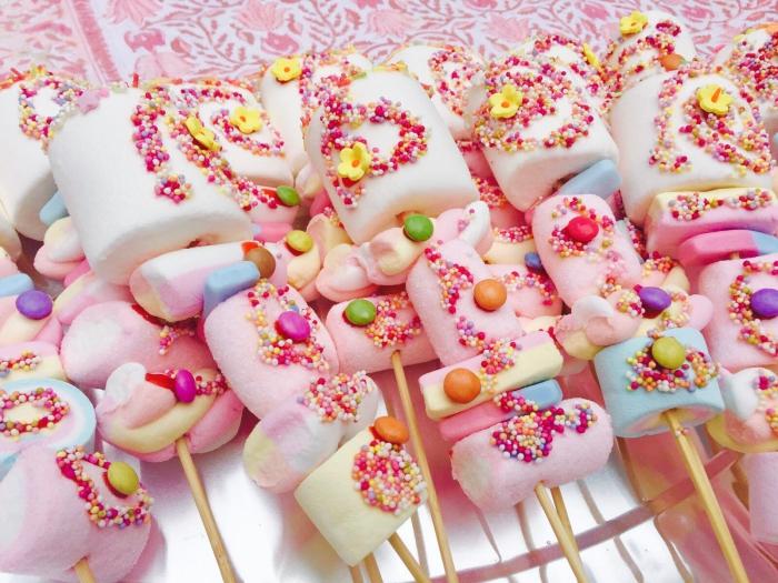 des brochettes à la guimauve en tons pastel décorées de sucre coloré parfaites pour un candy bar d'anniversaire
