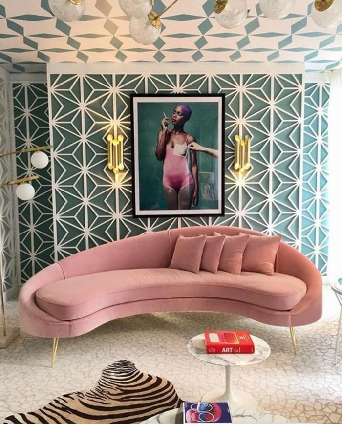 chambre rose et gris, canapé en forme semi-ronde en velours en couleur rose pale, murs arty excentriques en vert avec des formes triangulaires et de losanges en blanc
