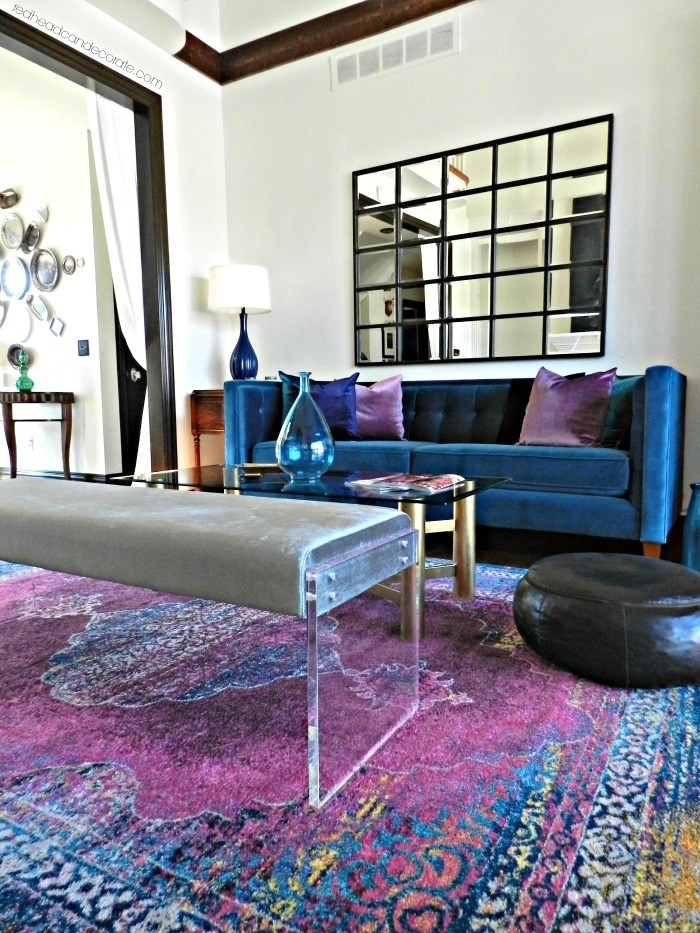 les matières sensuelles et la palette de luxe associant bleu roi, violet, blanc et noir apporte un aspect élégant au salon, canapé velours bleu marine saturé qui reprend les couleurs du tapis persan