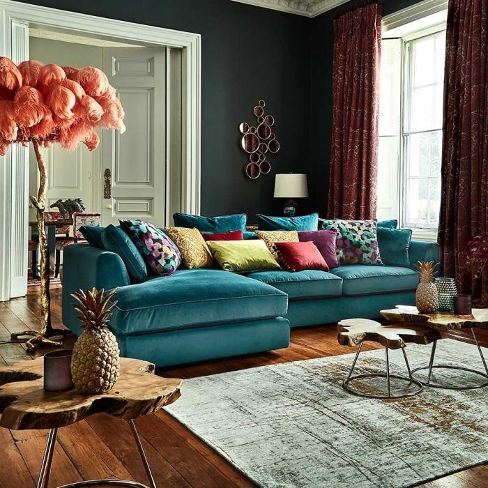 canapé en velours bleu paon accessoirisé avec une multitude de coussins aux nuances de l'ocre, bleu et violet, salon de luxe en vert, bleu et terracotta