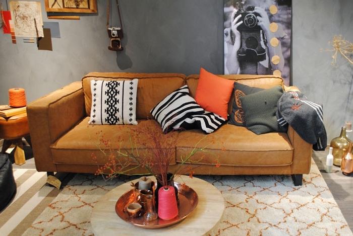 design intérieur moderne et traditionnel dans un salon aux murs gris avec canapé de cuir camel et tapis rayé en blanc et beige