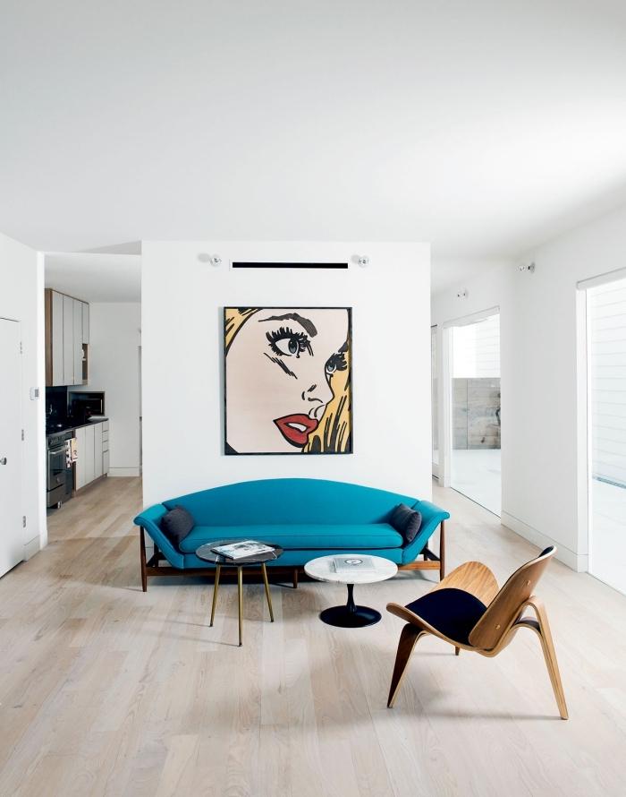 associé avec un tableau pop art original et sublimé par de petites tâches de noir, le canapé bleu canard se fait élément central dans ce salon blanc immaculé