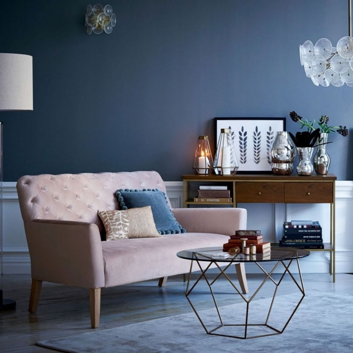 ambiance élégante et feutrée dans ce salon couleur bleu nuit associé aux éléments en verre et à un canapé rose poudré