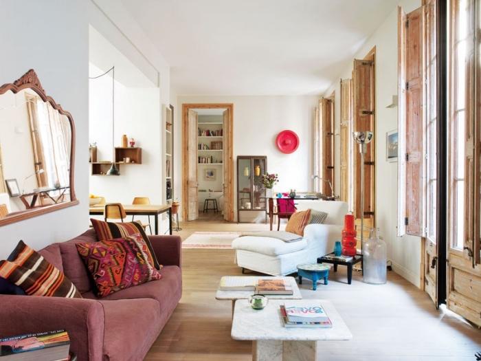 intérieur chaleureux dans un salon blanc avec fenêtres de bois et parquet clair, modèle de canapé rose couvert de coussins ethniques