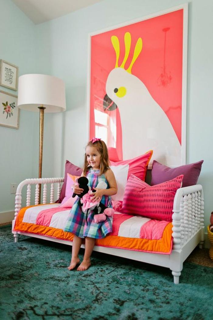 chambre montessori avec canapé blanc, grand tableau avec perroquet en cadre blanc, luminaire sur pied haut en métal couleur bronze avec abat-jour blanc