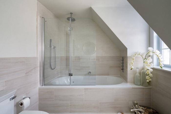 modèle de salle de bain mansardée au plafond blanc avec revêtement partiel en carrelage beige, salle de bain avec baignoire