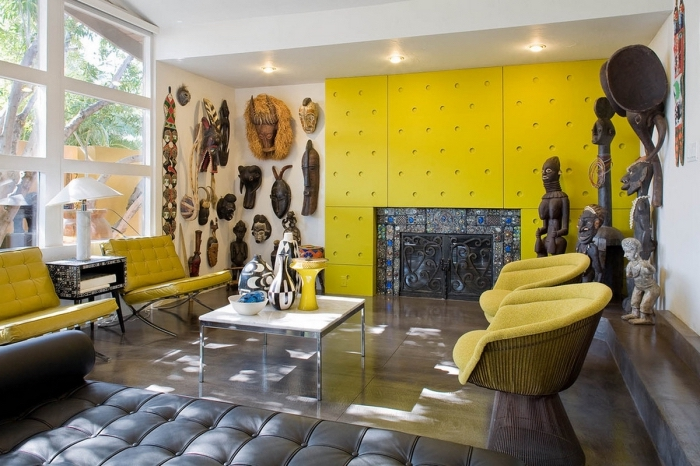 salon aux motifs africains avec panneaux de mur de couleur jaune moutarde, sculptures et masques tribaux