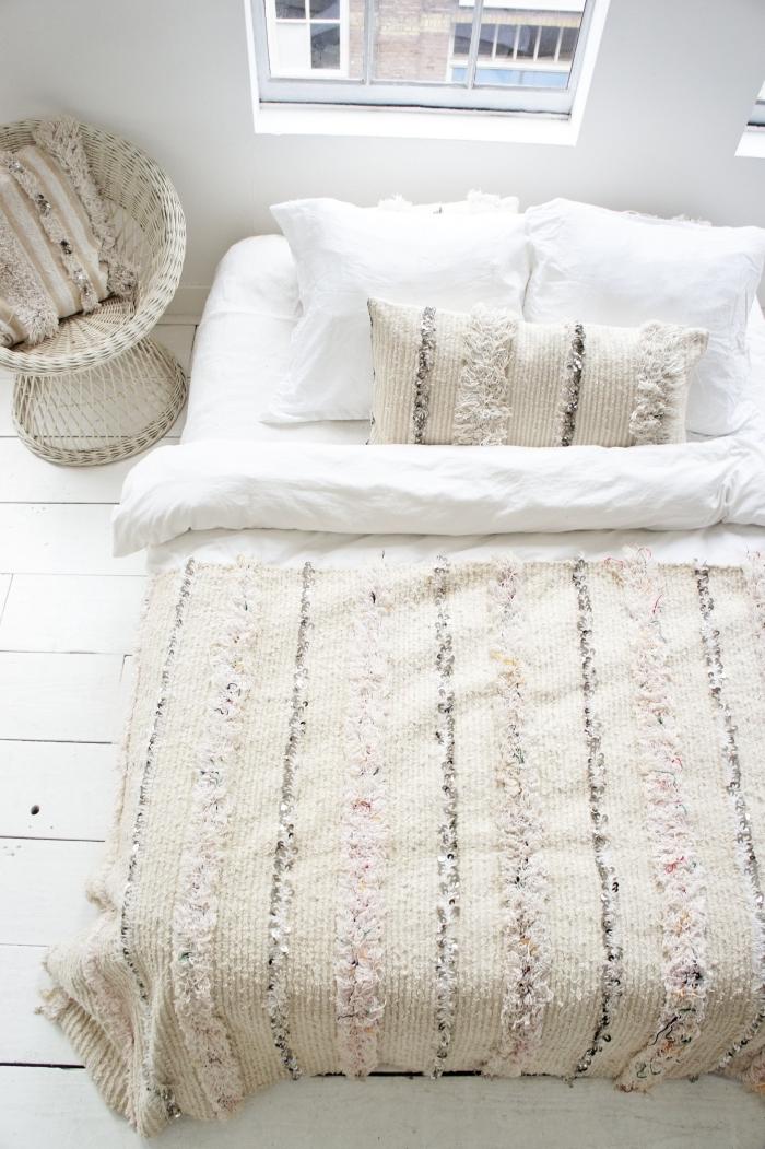 ambiance cocooning dans une chambre fille aménagée de style boho chic moderne avec peinture murale blanche et accessoires beige