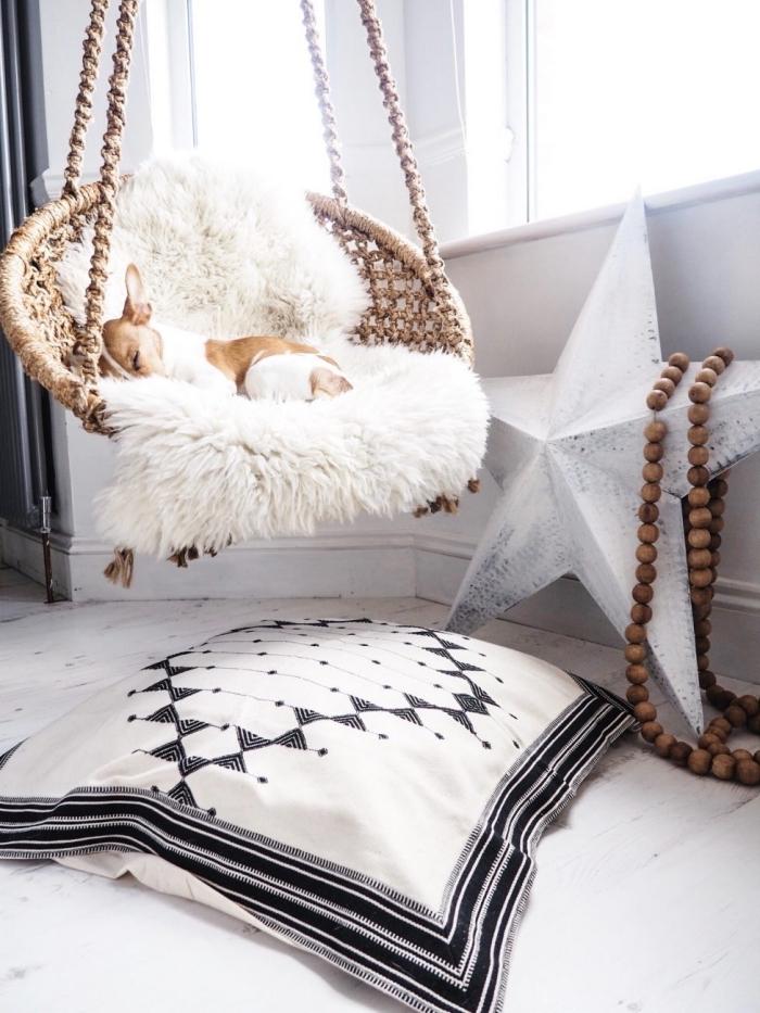 ambiance cozy dans une chambre aménagée de style boho avec chaise suspendue couvert de housse en fausse fourrure blanche