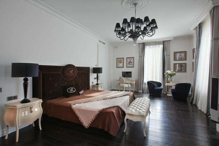 lit wengé, commode couleur crème, lampes de chevet noires, plafonnier baroque, banquette de lit blanche, sol en bois wengé