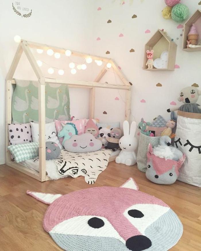 chambre rose et gris, tapis en forme de visage de renard en couleur rose pale, lit cabane Montessori en bois clair, recouvert de coussins en forme de nuages, étagères casiers en bois clair
