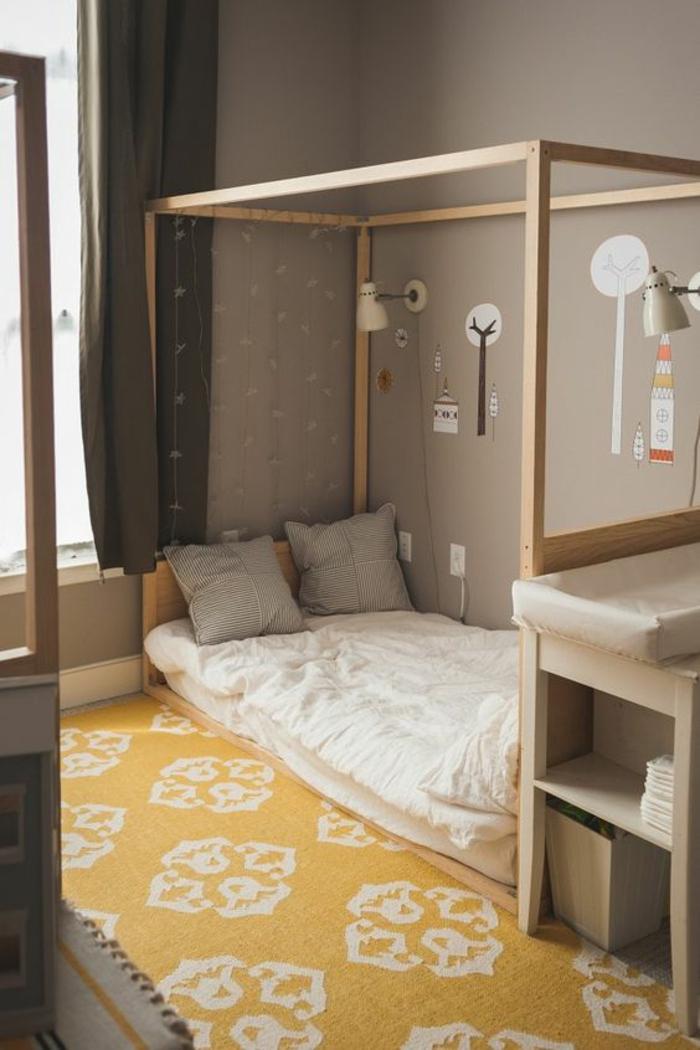 lit bébé sans barreau, tapis en jaune et blanc, aux motifs arabesques, lit cabane montessori, meuble pour changer les couches de bébé, murs en taupe