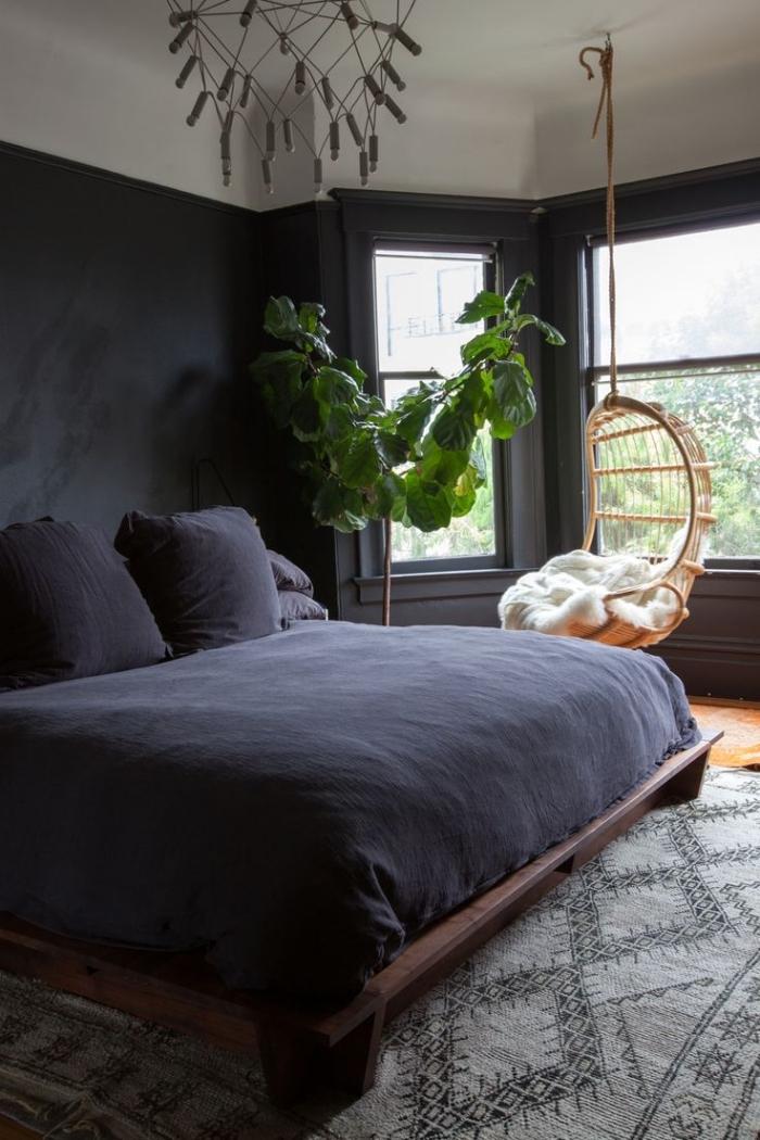 idée comment décorer une pièce aux murs foncés, modèle de design intérieur style bohème chic avec chaise oeuf suspendu et plante verte exotique