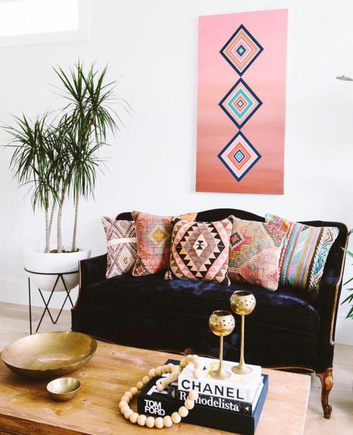 panneau décoratif rectangulaire en couleur rose pale avec des motifs ethniques, canapé en velours bleu roi, table en bois clair, murs blancs