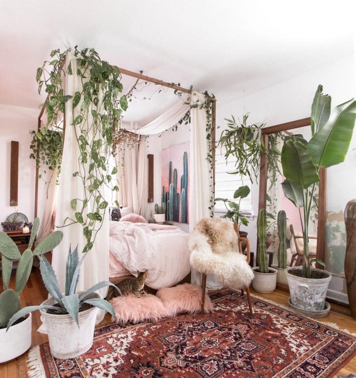 ambiance exotique dans une chambre à deco boheme chic avec cadre de lit bois et baldaquin décoré de plantes vertes