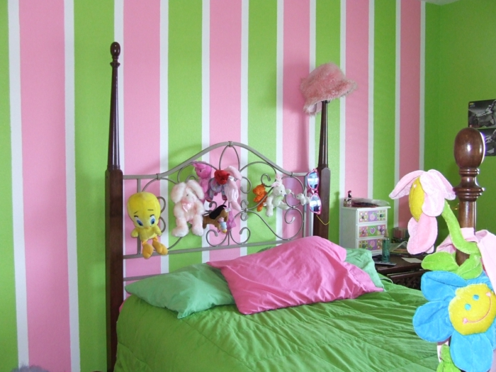 chambre rose poudré, rayures verticales en rose poudré et réséda au mur, couverture de lit en vert pomme, avec deux coussins en vert pomme et un coussin en rose fuchsia