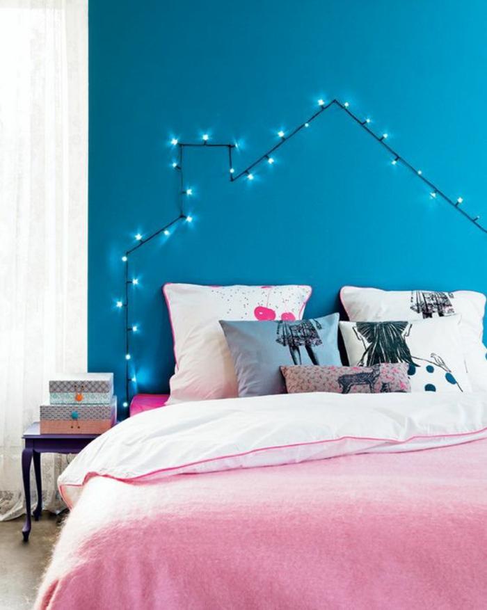 mur en bleu canard, guirlande suspendue au mur en forme de maison avec toit et cheminée, guirlande lumineuse pour chambre, lit adulte avec des coussins carrés de toute taille, linge de lit en rose