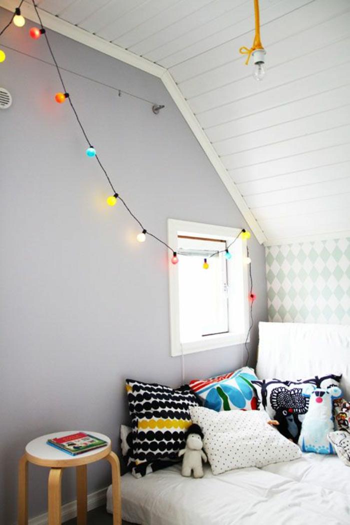 guirlande lumineuse chambre suspendue sur un mur en gris perle, espace sous les combles, plafond revêtu en éléments en bois peint en blanc