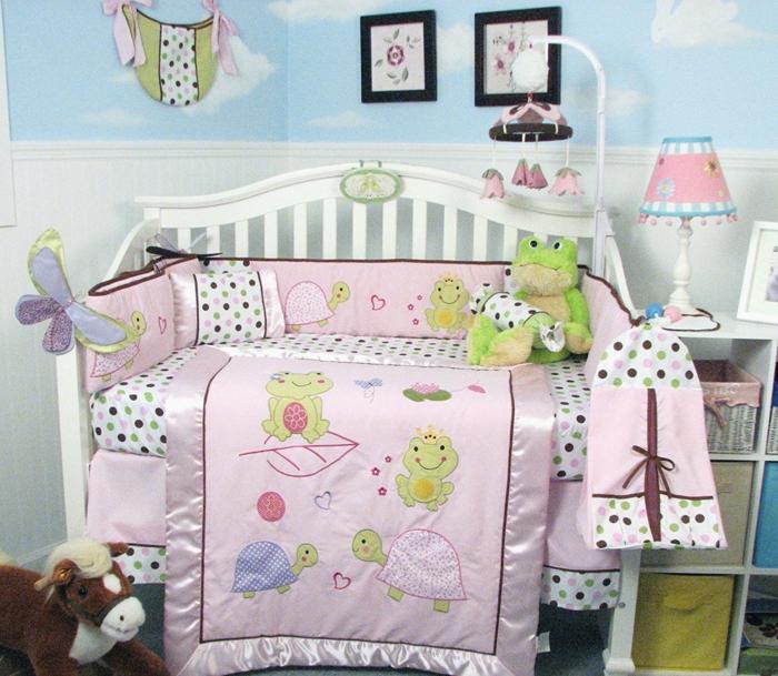 chambre de bébé, lit blanc aux barreaux, murs en papiers peints bleu pastel aux motifs nuages blancs, deux petits tableaux aux cadres noirs, petit luminaire avec abat-jour rose et blanc, paniers de rangement en tissu réséda et bleu ciel, couleur rose pale
