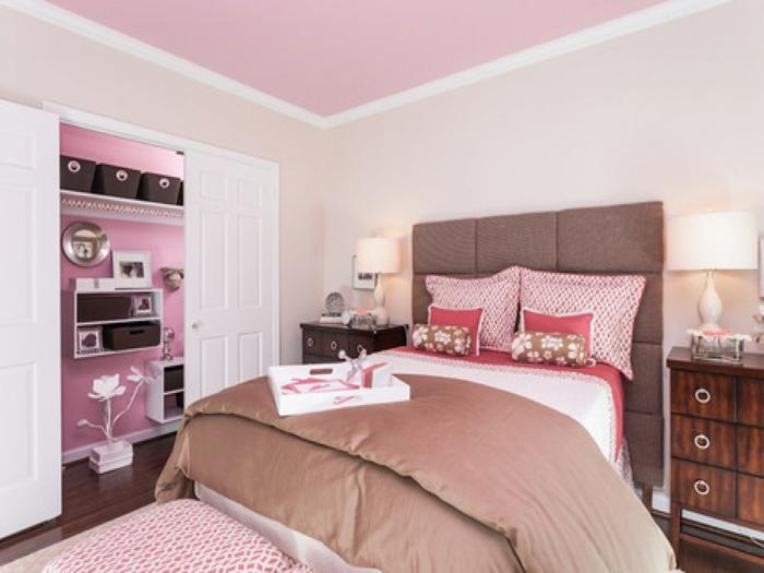 couleur rose pale, rose poudree, chambre rose et gris, murs blancs, grande tete de lit en marron, formée de petits panneaux mis ensemble, meuble de rangement massif avec des poignées rondes en métal clair