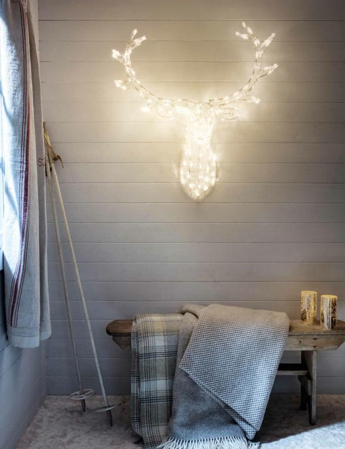 déco scandinave, murs blancs, tete de cerf en métal, illuminée par une guirlande enroulée dans le métal, guirlande lumineuse pour chambre