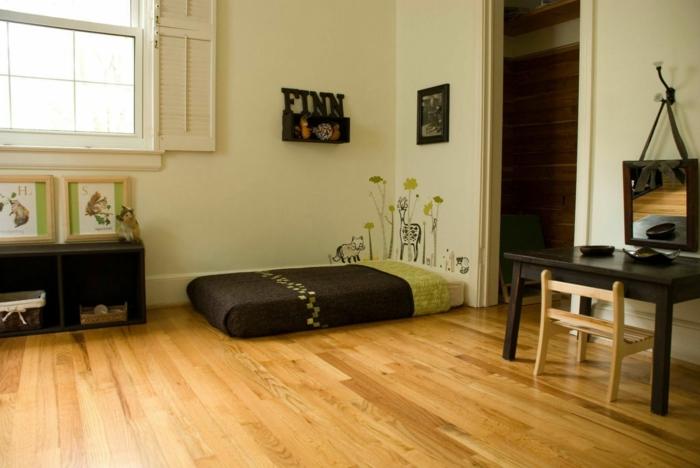 murs en vert réséda, parquet encastrable en marron et jaune, lit bébé sans barreau, grande fenêtre au cadre en jaune, table en bois noir laqué et chaise en bois clair avec dossier