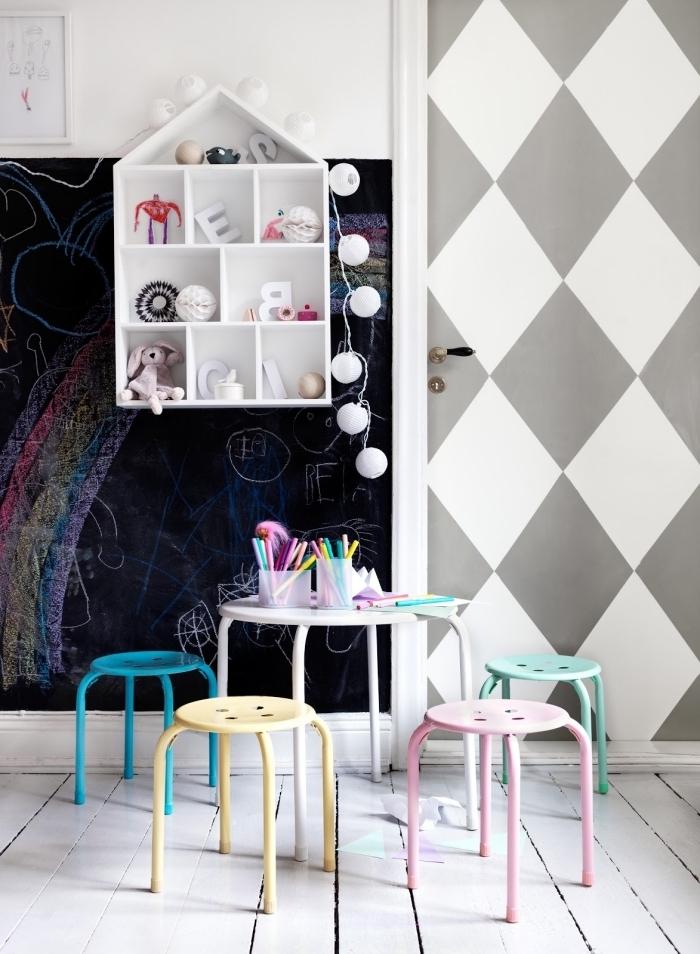 une jolie décoration de porte avec des motifs losanges peints en blanc et gris qui s'harmonisent avec le tableau d'école en ardoise et l'ambiance scandinave de cette chambre d'enfant nordique
