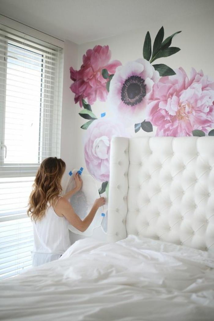 mur en peintures fleuries en couleur rose poudré, lit avec grande tete en tissu blanc satiné avec effet matelassé, stores blanches pour les fenêtres