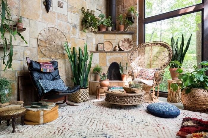 décor chic ethnique dans une pièce large aux murs en pierre avec étagères de bois foncé et chaises et table en rotin