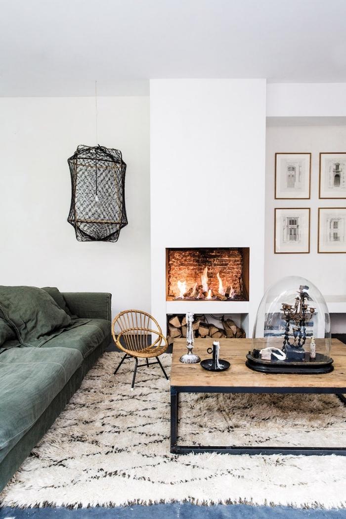 déco de salon chaleureux aux murs blancs avec petite cheminée au centre, déco murale avec cadres photos
