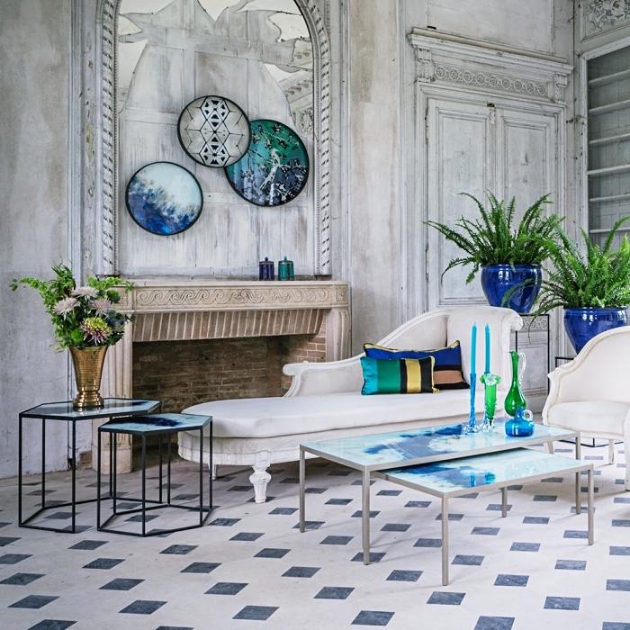 exotisme dans un salon large aux murs vintage aménagé avec éléments ethniques de couleurs turquoise vert et bleu