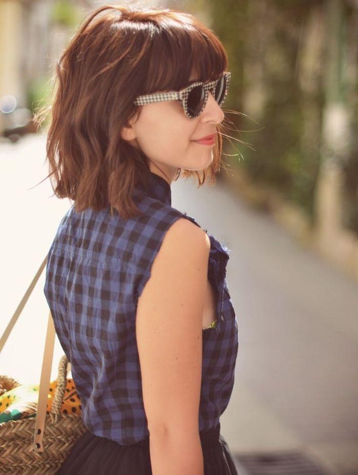 coupe carré avec frange longue, mèches de cheveux chatain ondulées, chemise sans manches, jupe plissée