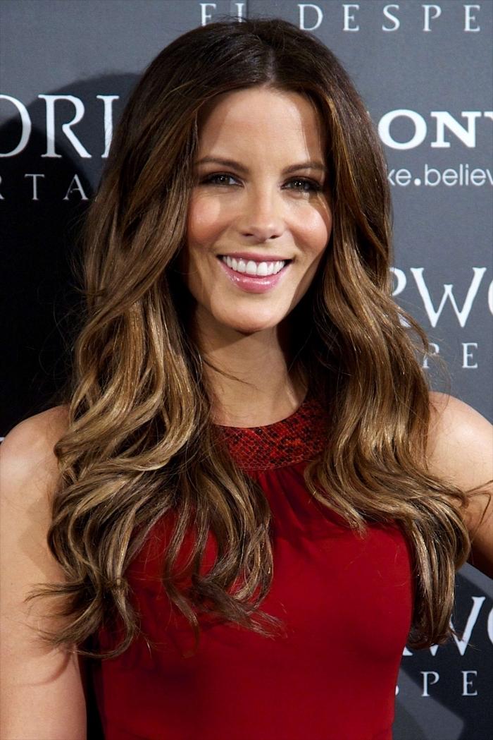 coiffure célébrité de Kate Beckinsale aux cheveux longs ondulés, modèle de robe rouge, meche sur cheveux chatain