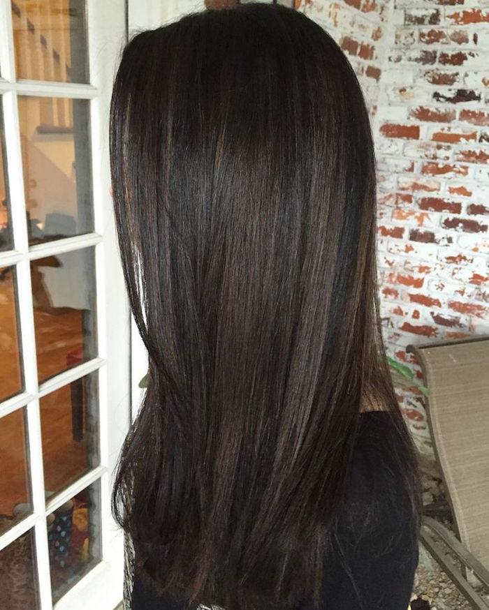 femme aux longs cheveux bruns foncés avec léger balayage clair glacé