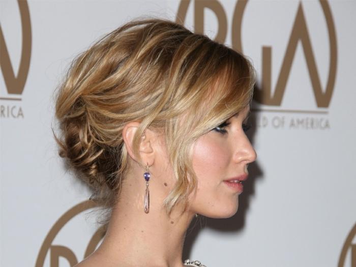 Jennifer Lawrence avec un chignon bas flou, mèches autour du visage, chignon volumineux