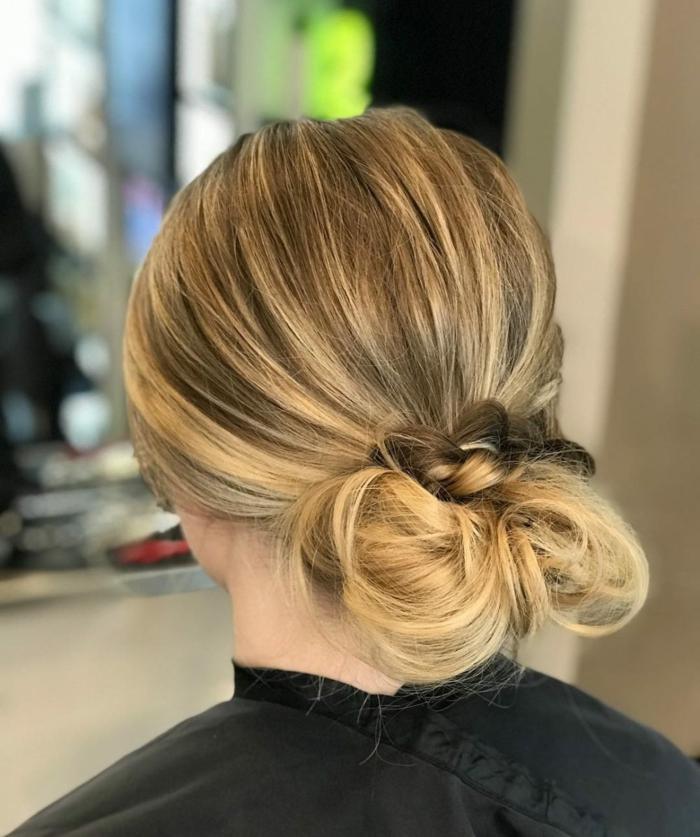chignon bas flou avec une tresse, cheveux couleur bronde, balayage subtil
