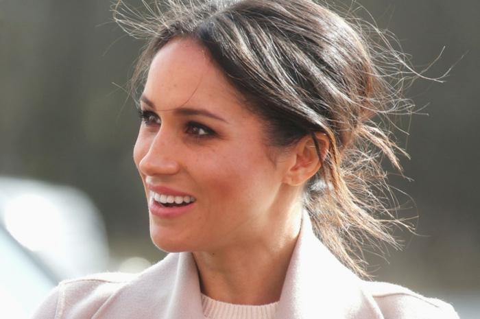 Meghan Markle avec un chignon coiffé décoiffé, tenue en couleurs douces et neutres