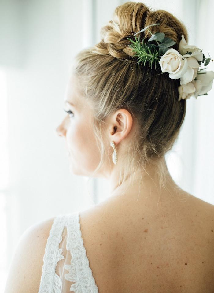chignon tressé haut, exemple de chignon classique entouré de tresse et une attache en fleurs fraiches