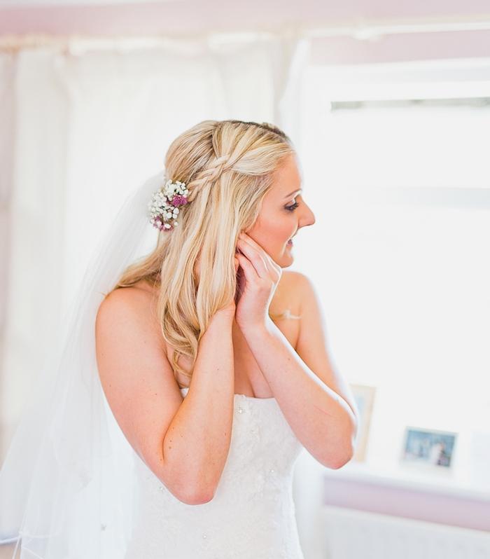 robe de mariée simple avec une demie tresse latérale, voile blanche et décoration accessoire fleurs fraiches