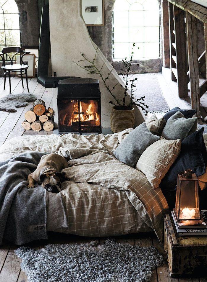 Aménagement chambre 10m2, deco chambre moderne style nordique, grand espace ouverte pour le salon, la chambre à coucher cosy, cheminée à bois, chien sur le lit, chambre rustique