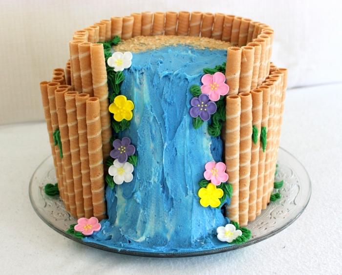 decoration gateau vaiana à deux étages couvert de sable en biscuits émiettés et cascade d'eau en crème au beurre et colorant turquoise