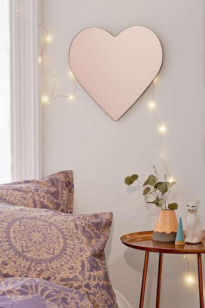 Aménager une chambre de 10m2, deco chambre moderne, cosy chambre à coucher, miroir coeur, guirlande lumineuse, plante verte dans une vase, chat céramique pour décoration de table de chevet originale