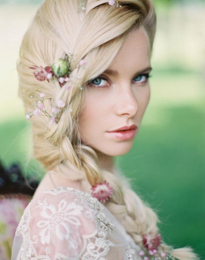 modèle de tresse sur le coté avec des fleurs champetres dans les cheveux, robe de mariée motifs floraux