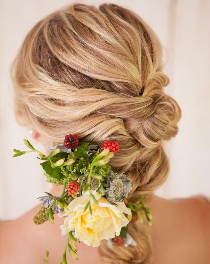 coiffure mariee avec une tresse noeud style décoiffé avec un bouquet de fleurs dans les cheveux