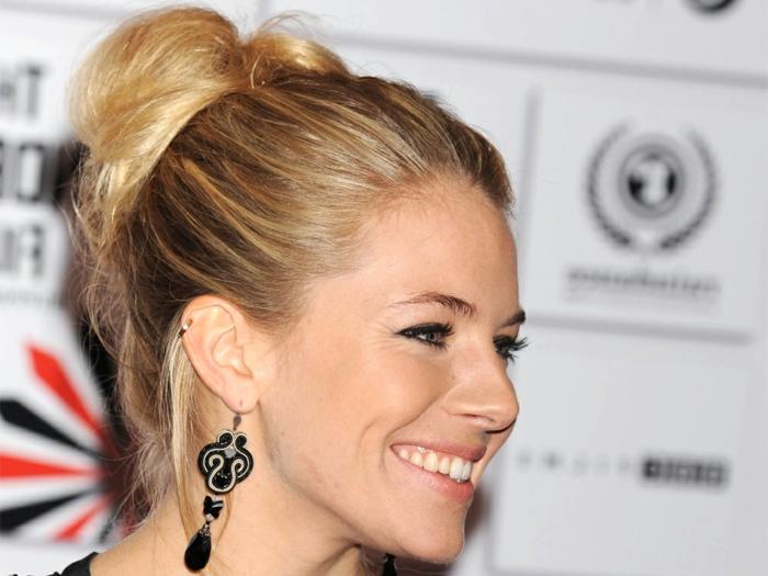 Sienna Miller avec des cheveux effet coiffé décoiffé, cheveux blonds, boucles d'oreilles pendantes