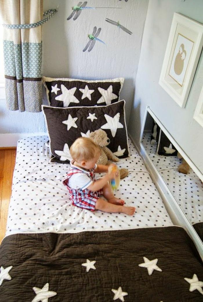 miroir montessori, lit bébé sans barreau, deux grands coussins marron avec des étoiles blanches, murs en couleur lavande, rideaux couleur crème et bleu pastel a pois